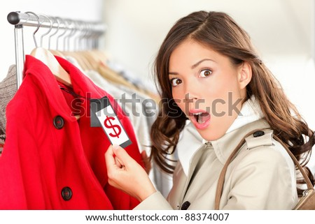 shopping woman shocked and surprised over price looking at price tag on coat or jacket. Woman shopper shopping for clothes inside in clothing store. Funny image of Asian / Caucasian female model. - stock photo