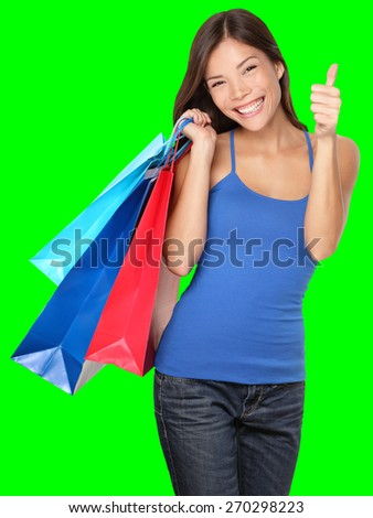 Shopping woman showing thumbs up success holding shopping bags isolated on green background. Beautiful young mixed race Asian Caucasian female shopper. - stock photo