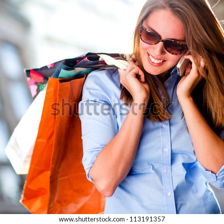 Shopping woman talking on the phone looking happy - stock photo