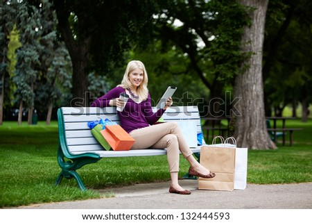 Shopping Woman Using Digital Tablet on bench. - stock photo