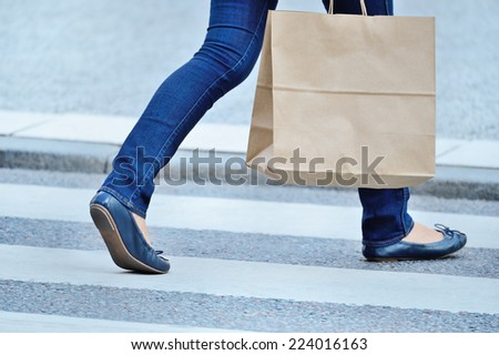 Shopping woman walking cross the street - stock photo