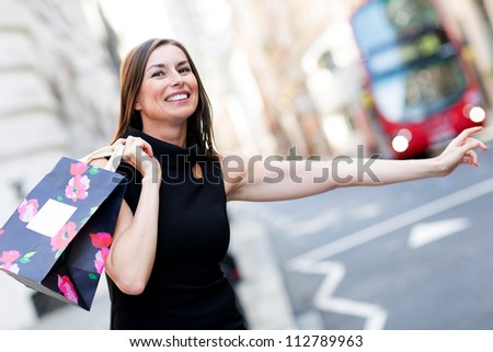 Shopping woman with her arm extended grabbing a taxi - stock photo
