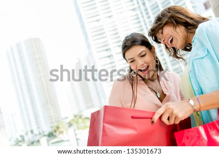Shopping women looking at purchases in a bag and smiling - stock photo