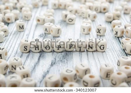 Shopping word written on wood block. - stock photo