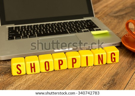 Shopping written on a wooden cube in a office desk - stock photo