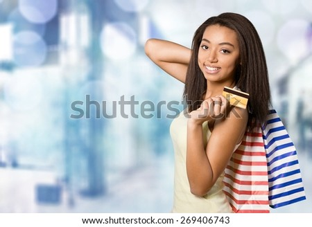 Shopping. Young woman holding credit card and carrying shopping bags - stock photo
