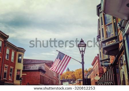 Shops along main street, Galena, Illinois, focus on flag, vintage toned image. - stock photo