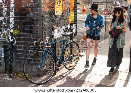 Shoreditch, London, UK, September 28 2014: Two stylish hipster girls walking in Shoreditch. Shoreditch is one of London's most distinctive areas, home of trendy bars, artists and fashionistas. - stock photo