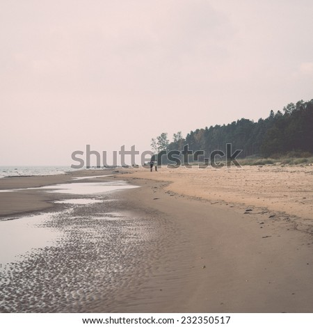 Shoreline of Baltic sea beach with rocks and sand dunes under clouds. Vintage effect. - stock photo