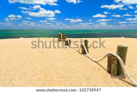 Shoreline of the Florida Keys with sailboat in the background against a blue sky. - stock photo
