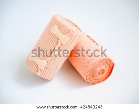 Short and long elastic bandage on white background - stock photo