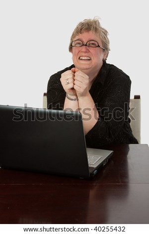 Short hair blond caucasian woman sitting at desk in front of a laptop computer wearing eyeglasses upside-down with a happy excited facial expression looking up - stock photo
