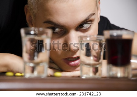 Short hair drunk young girl looking at alcohol shooters with lust. Selective focus on girl - stock photo