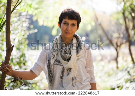 Short haired, brown eyed girl posing in the park in autumn  - stock photo