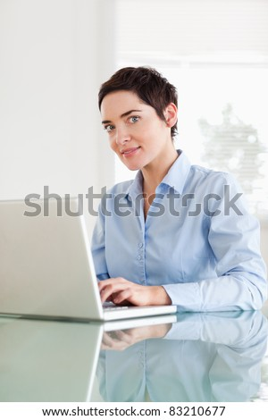 Short-haired businesswoman with a laptop looking into the camera in an office - stock photo