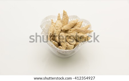 Short sticks cookies powdered with ground nuts on paper doilies paper in glass bowl.  Isolated on white background. - stock photo