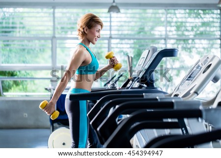 Shorthaired young woman doing exercises with dumbbells as additional weight while walking on treadmill in gym - stock photo