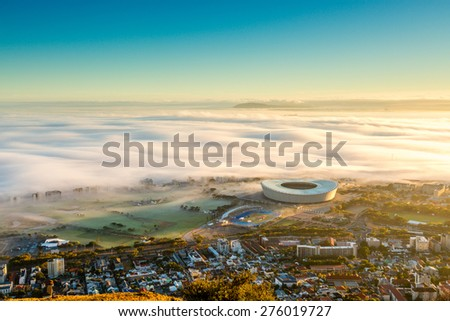 Shortly after sunrise in Cape Town, the fog arrives from the sea and envelops the lower part of the city- including the stadium. - stock photo