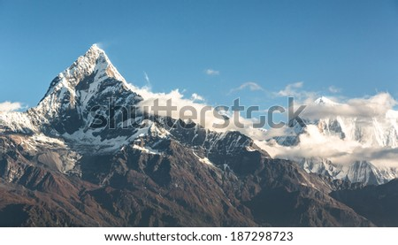 Shot during an ultra light plane flying over the Annapurna mountain range in the Himalayas near Pokhara, Nepal. The summit on the left is the Machapuchare (6993m), aka the fishtail mountain. - stock photo