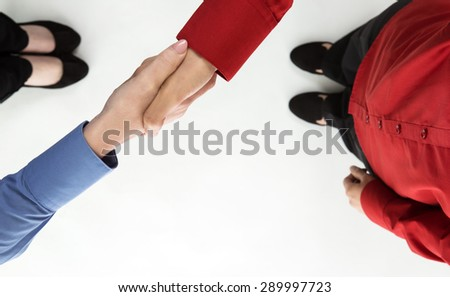 shot from above of two female business women shaking hands as they meet - stock photo