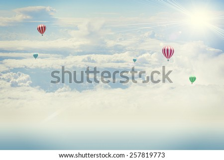 Shot from an airplane. Background of clouds and sun with hot air balloon - stock photo
