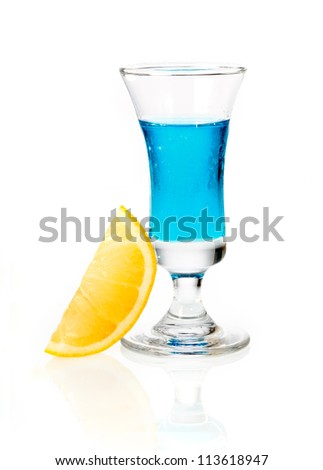 Shot glass of blue curacao liqueur with orange garnish on a white reflective background - stock photo