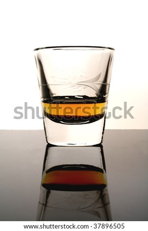Shot glass with whiskey  against black background. - stock photo