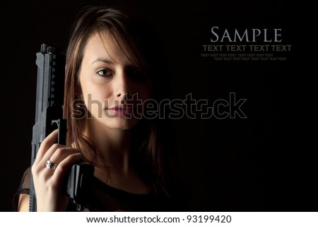 Shot of a beautiful girl holding gun, isolated on black bckground - stock photo