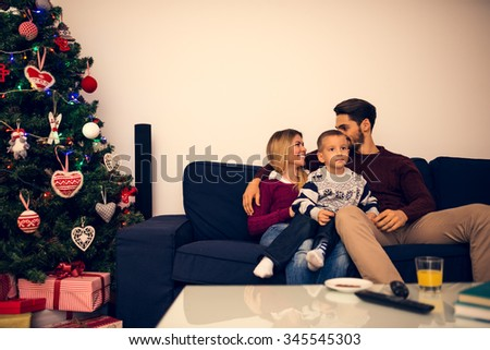 Shot of a beautiful happy family sitting on a sofa in living room. - stock photo