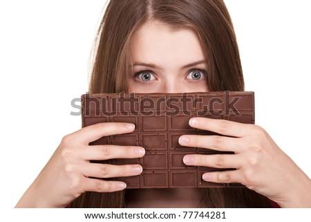 Shot of a beautiful teen girl holding big chocolate bar - stock photo