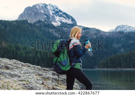 Shot of a beautiful  young woman with bottle of water enjoying the view while hiking - stock photo