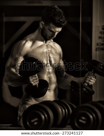 Shot of a Bodybuilder lifting dumbell in dramatic gym lighting - stock photo