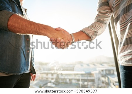 Shot of a businesspeople shaking hands in office with cityscape in background. Cropped image of two young male professionals hand shake after a deal. Focus on hands. - stock photo