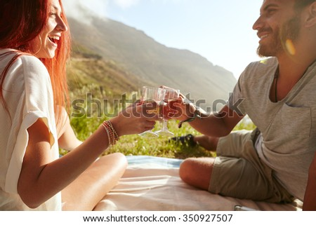 Shot of a cheerful young couple drinking wine and enjoying a picnic.  Young man with her girlfriend on vacation sitting on grass, toasting a glass of wine. - stock photo