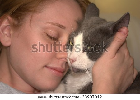 Shot of a cute girl and cat holding each other face to face - stock photo