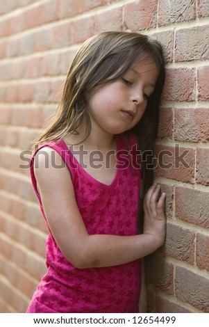 Shot of a depressed young girl against a brick wall - stock photo