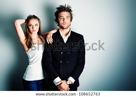Shot of a fashionable couple posing at studio. - stock photo
