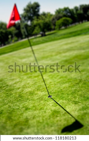 Shot of a golf hole with a flag - stock photo