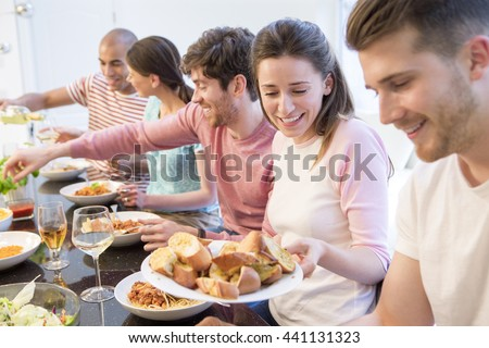 Shot of a group of friends sat down at a table serving dinner. - stock photo
