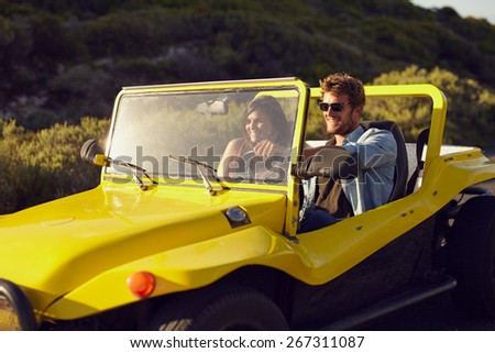 Shot of a handsome young man driving a car in the countryside with his girlfriend. Cheerful young couple on a road trip in a open topped vehicle. - stock photo
