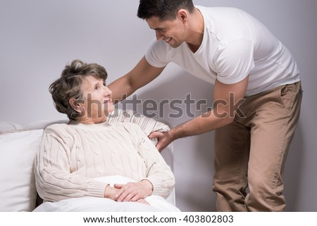 Shot of a happy young man helping his grandmother - stock photo