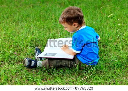 Shot of a little boy with a book having a rest outdoor. - stock photo