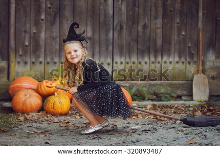 Shot of a little girl in halloween costume posing with broom and pumpkins during Halloween party - stock photo
