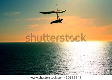 Shot of a man hang gliding in Northern California over the beach. - stock photo