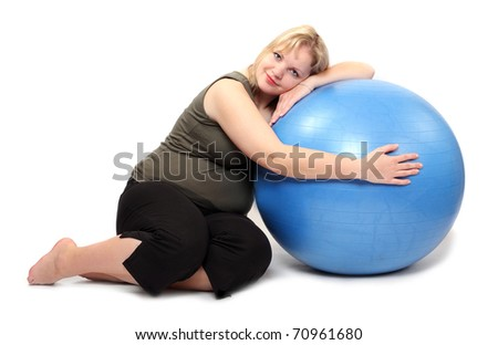 Shot of a overweight young woman with blue ball on a white background. - stock photo