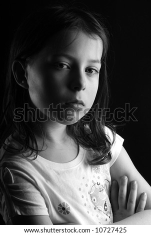 Shot of a pretty seven year old girl looking directly at the camera with her arms crossed, against a black background - stock photo