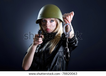 Shot of a sexy fashion style attractive woman portrait point on you with gun in military uniform, wearing black leather jacket, posing against black background with make up. - stock photo
