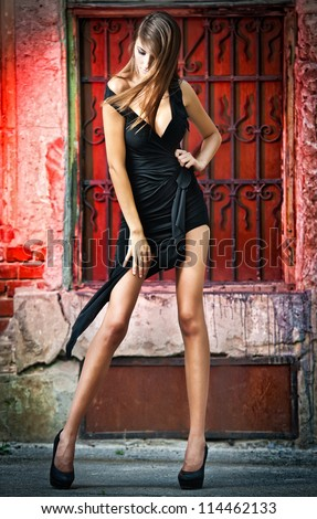 Shot of a sexy high fashion woman posing outdoor. Cute brunette with black dress posing on a city street - stock photo
