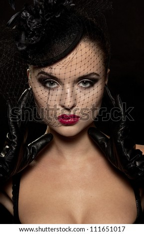 Shot of a sexy woman in black over black background. - stock photo