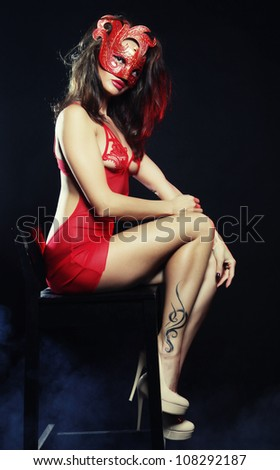 Shot of a sexy woman in erotic lingerie with mask - stock photo